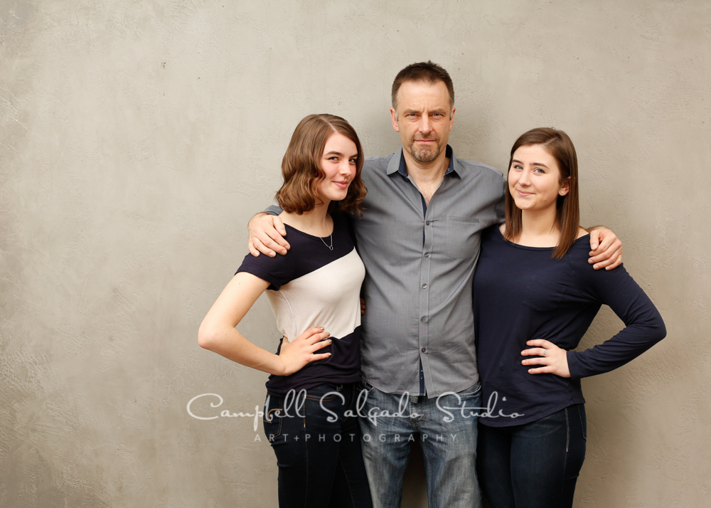 Portrait of father and daughters on modern grey background by family photographers at Campbell Salgado Studio, Portland, Oregon.