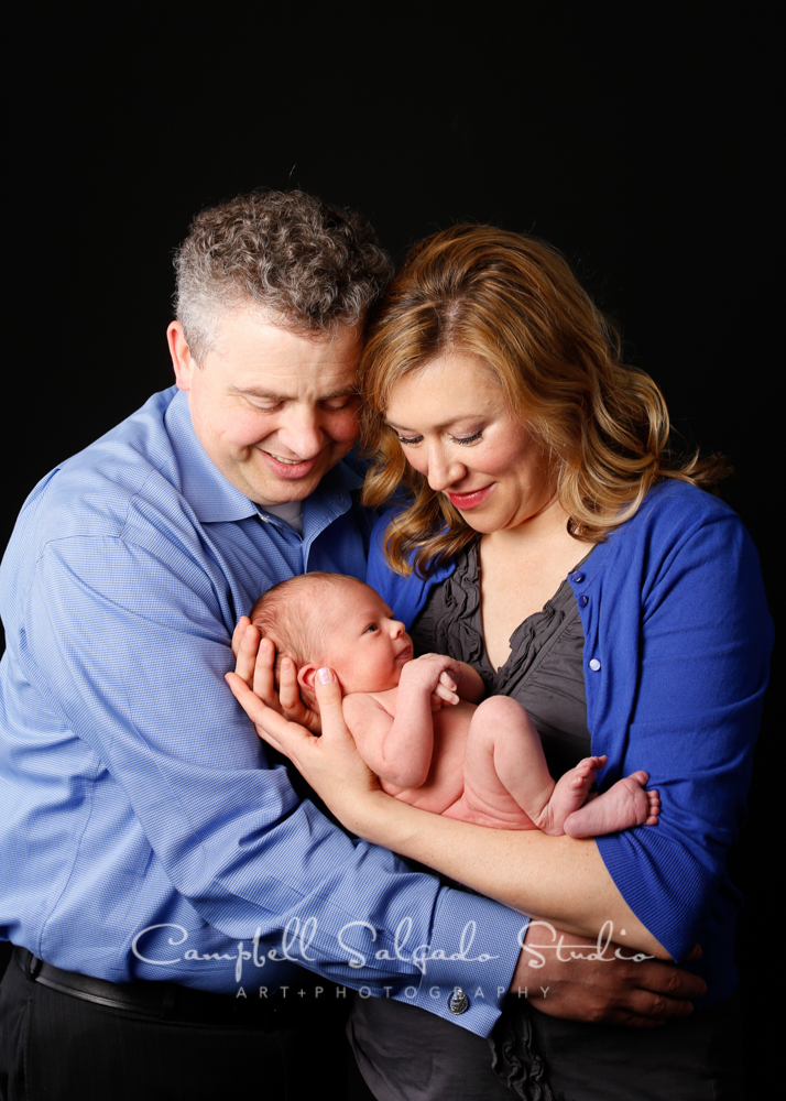 Portrait of new family on black background by newborn photographers at Campbell Salgado Studio, Portland, Oregon.
