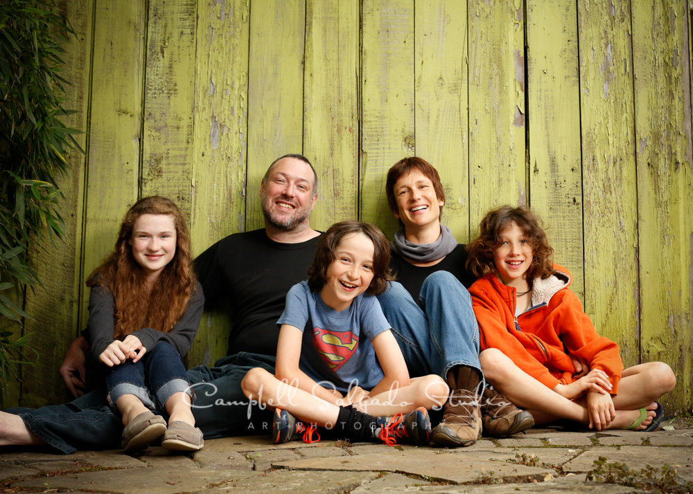 Portrait of family on lime fenceboard background by family photographers at Campbell Salgado Studio, Portland, Oregon.