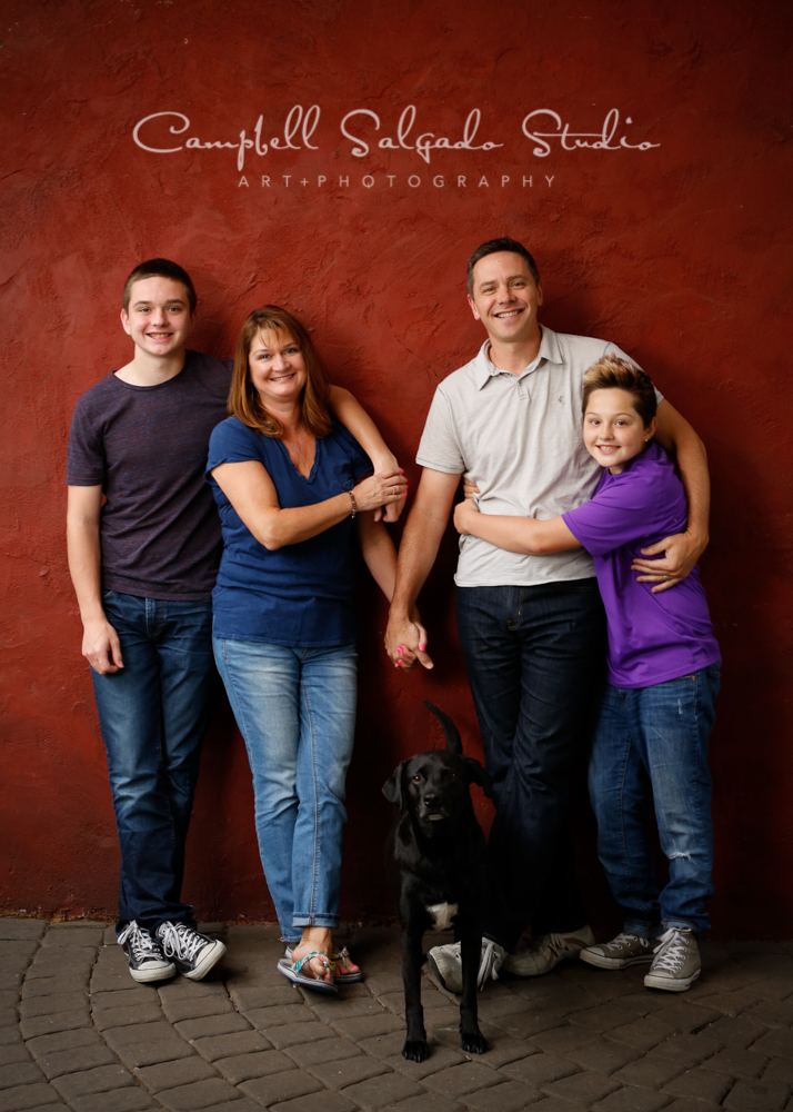 Portrait of family on red stucco background by family photographers at Campbell Salgado Studio, Portland, Oregon.