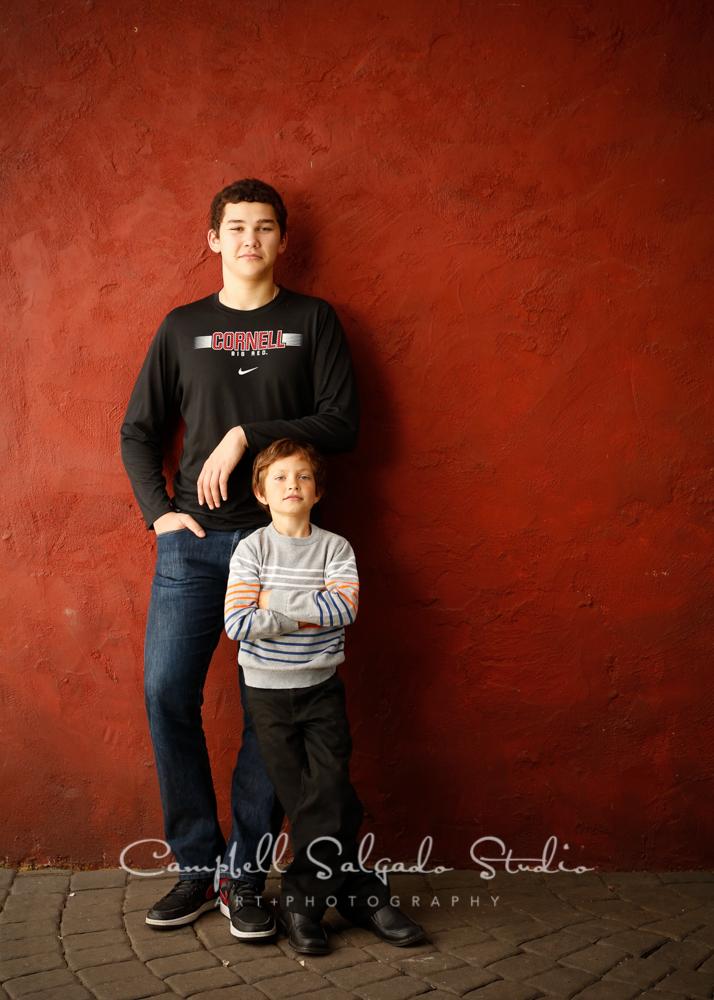Portrait of cousinson red stuccobackgroundby family photographers at Campbell Salgado Studio, Portland, Oregon.