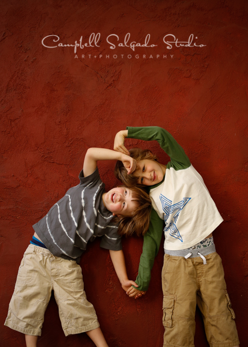 Portrait of boys on red stucco background by kids photographers at Campbell Salgado Studio, Portland, Oregon.