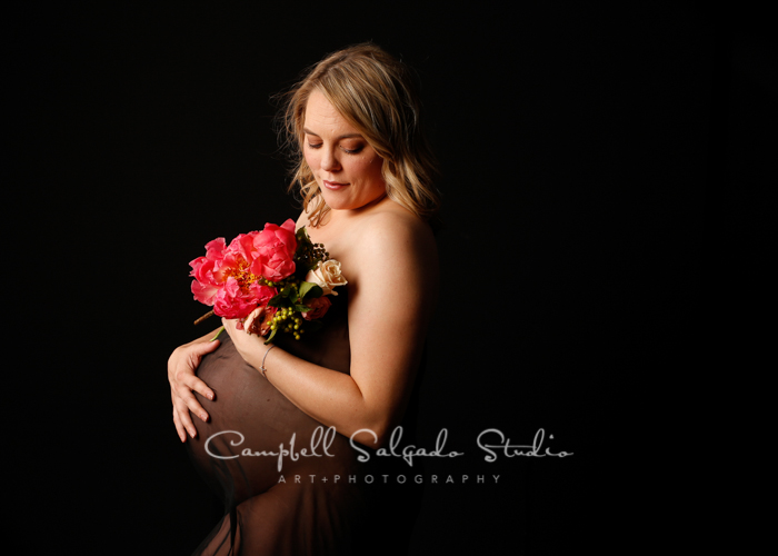 Maternity portrait of woman on black background by maternity photographers at Campbell Salgado Studio, Portland, Oregon.