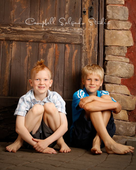 Portrait of brothers on rustic door background by family photographers at Campbell Salgado Studio, Portland, Oregon.