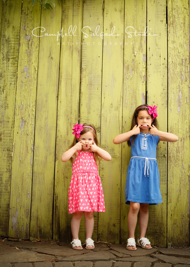Portrait of sisters on lime fence boards background by family photographers at Campbell Salgado Studio, Portland, Oregon.