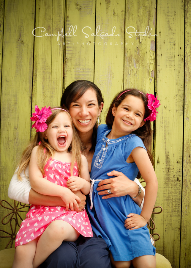 Portrait of mother and daughters on lime fence boards background by family photographers at Campbell Salgado Studio, Portland, Oregon.