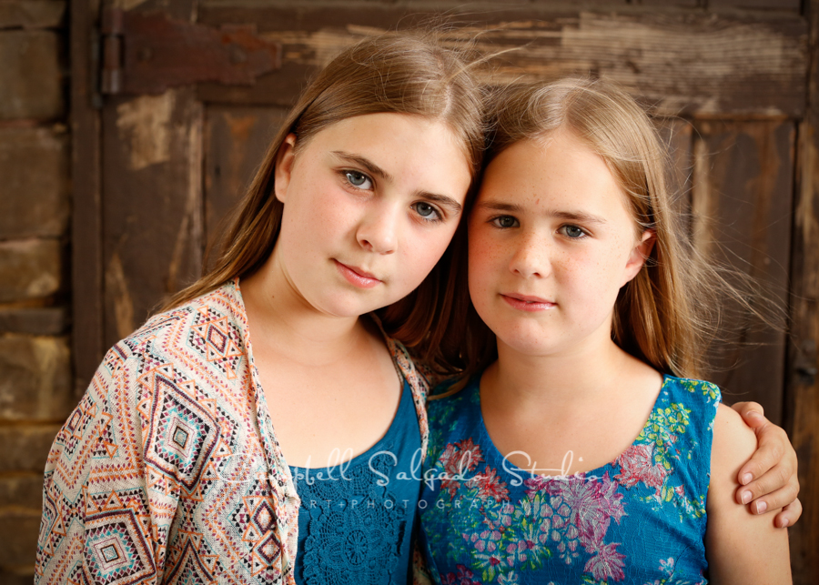 Portrait of sisters on rustic door background by child photographers at Campbell Salgado Studio, Portland, Oregon.