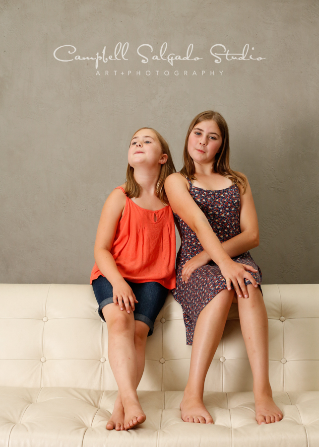 Portrait of sisters on modern grey background by child photographers at Campbell Salgado Studio, Portland, Oregon.