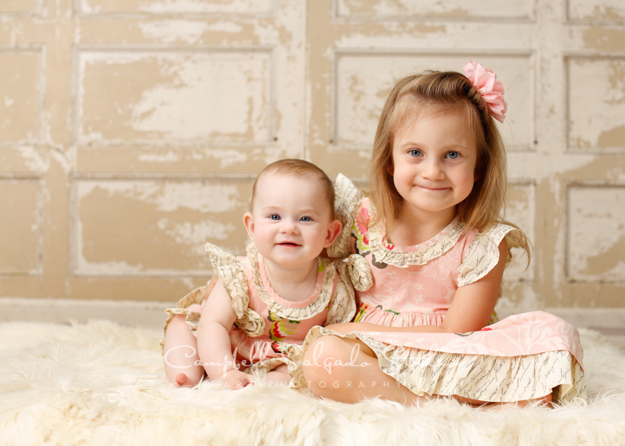 Portrait of sisters on antique ivory doors background by childrens photographers at Campbell Salgado Studio, Portland, Oregon.