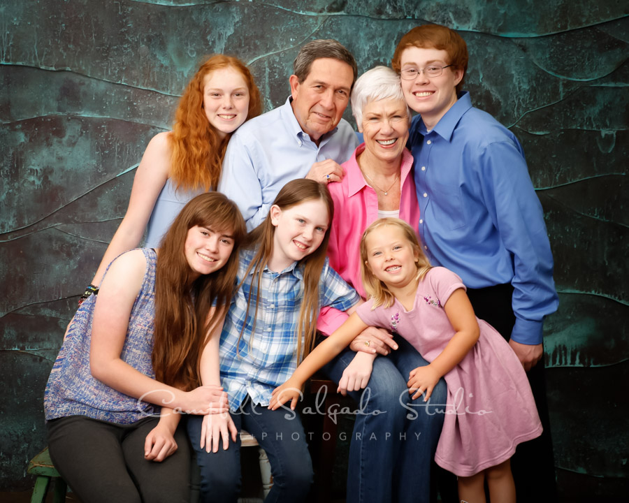 Portrait of multi-generational family on copper wave background by family photographers at Campbell Salgado Studio.