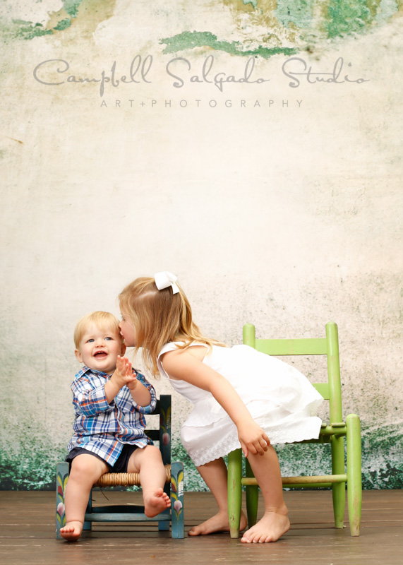 Portrait of a sister kissing baby brother by children's photographers at Campbell Salgado Studio, Portland, Oregon