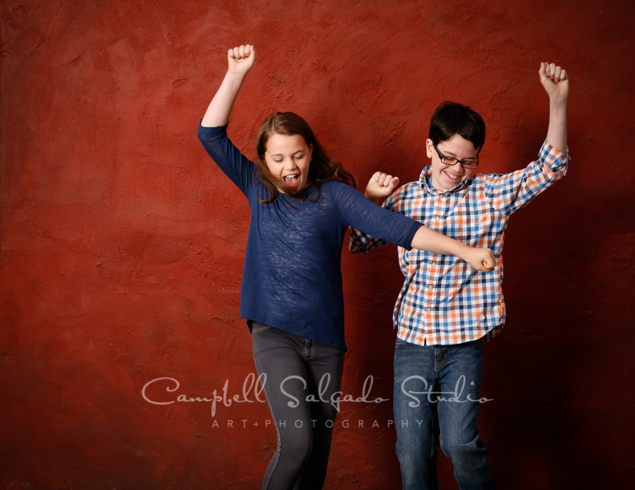 Portrait of siblings on red stucco background by children's photographers at Campbell Salgado Studio in Portland, Oregon.