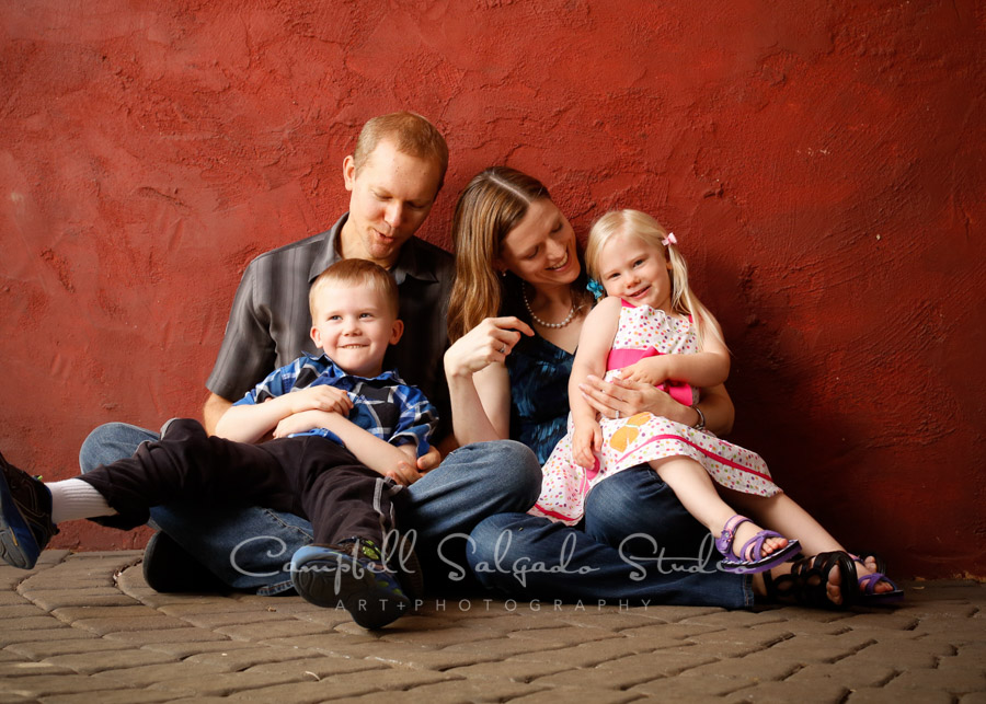 Portrait of family on red stucco background by family photographers at Campbell Salgado Studio in Portland, Oregon.