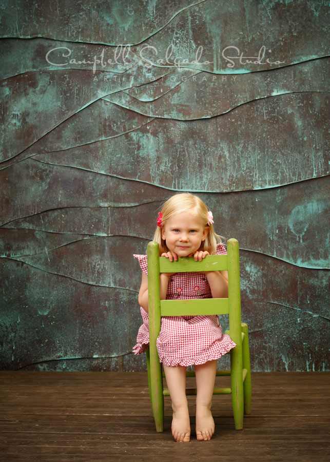 Portrait of girl on copper wave background by child photographers at Campbell Salgado Studio in Portland, Oregon.