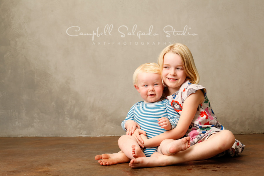 Portrait of siblings on modern grey background by children's photographers at Campbell Salgado Studio in Portland, Oregon.