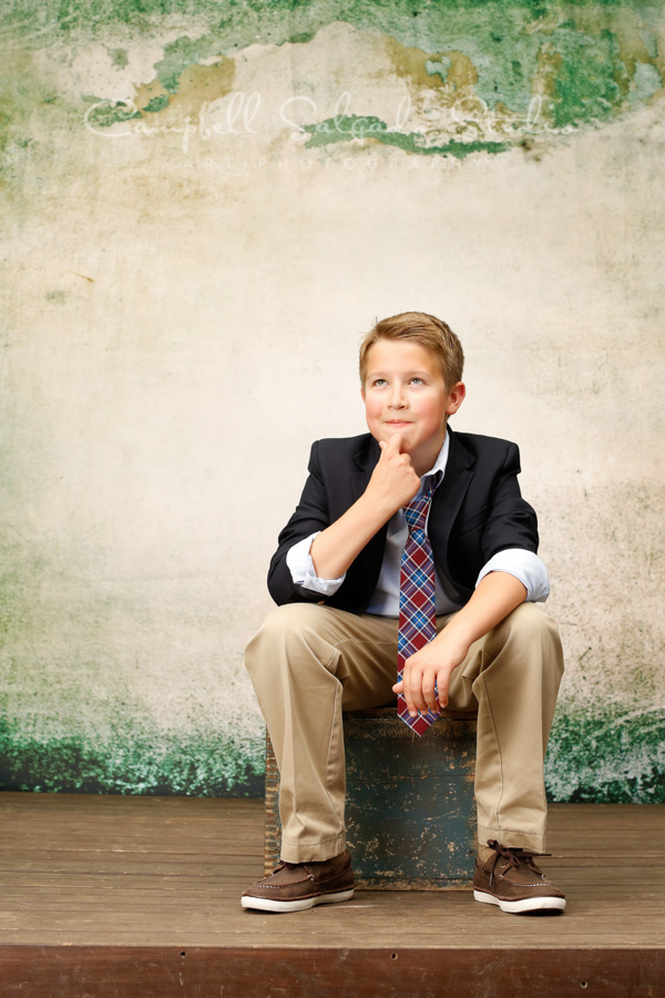 Portrait of boy on abandoned concrete background by child photographers at Campbell Salgado Studio in Portland, Oregon.