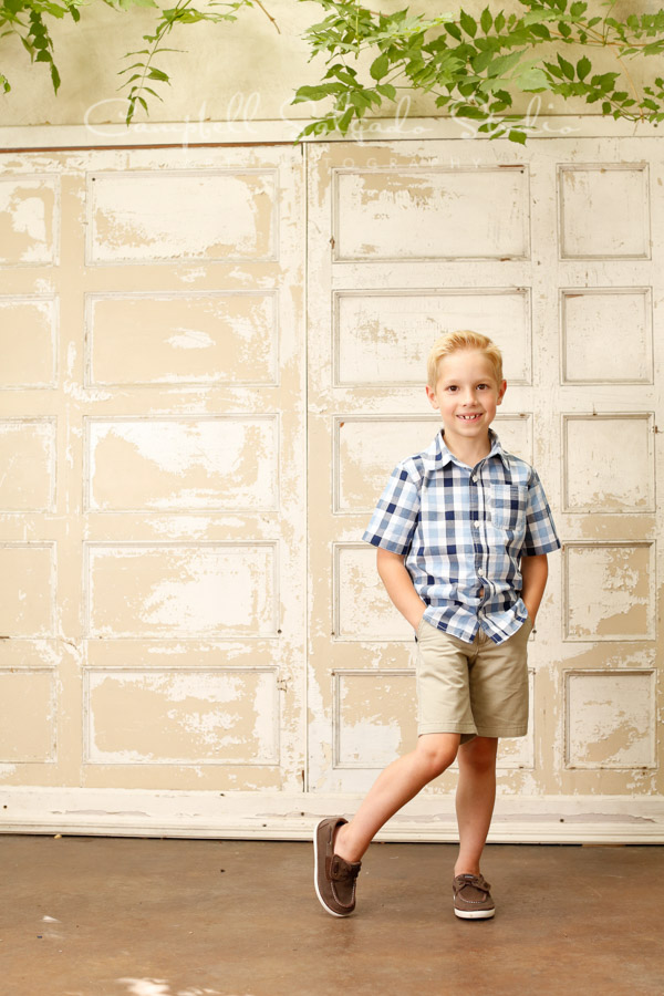 Portrait of boy on antique white doors background by child photographers at Campbell Salgado Studio in Portland, Oregon.