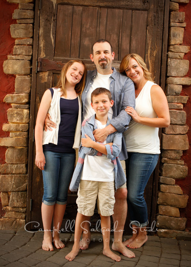 Portrait of family on rustic door background by family photographers at Campbell Salgado Studio in Portland, Oregon.