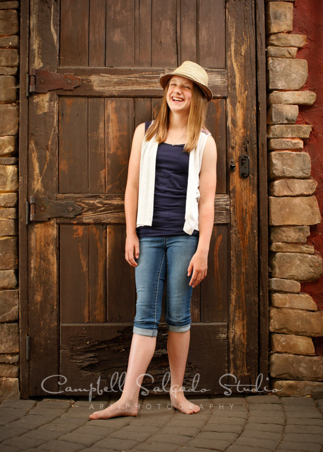 Portrait of girl on rustic door background by child photographers at Campbell Salgado Studio in Portland, Oregon.