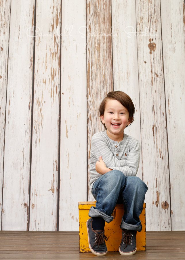 Portrait of child on white fence boards background by child photographers at Campbell Salgado Studio in Portland, Oregon.