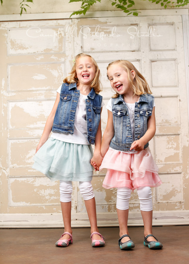 Portrait of twins on antique ivory doors by childrens photographers at Campbell Salgado Studio in Portland, Oregon.