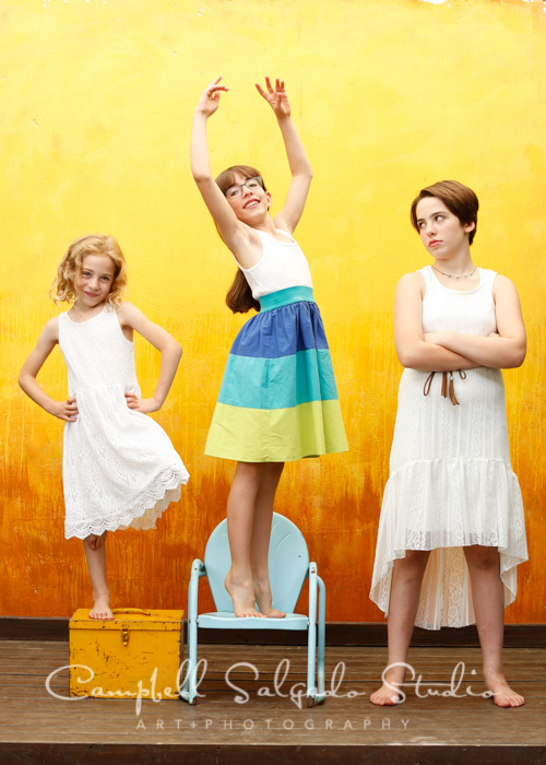 Childrens photographers at Campbell Salgado Studio photograph three sisters against a yellow background.