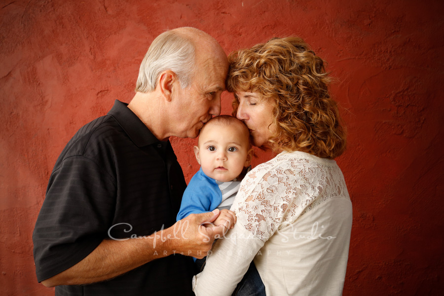 Portrait of grandparents and grandson on red stucco background by family photographers at Campbell Salgado Studio in Portland, Oregon.