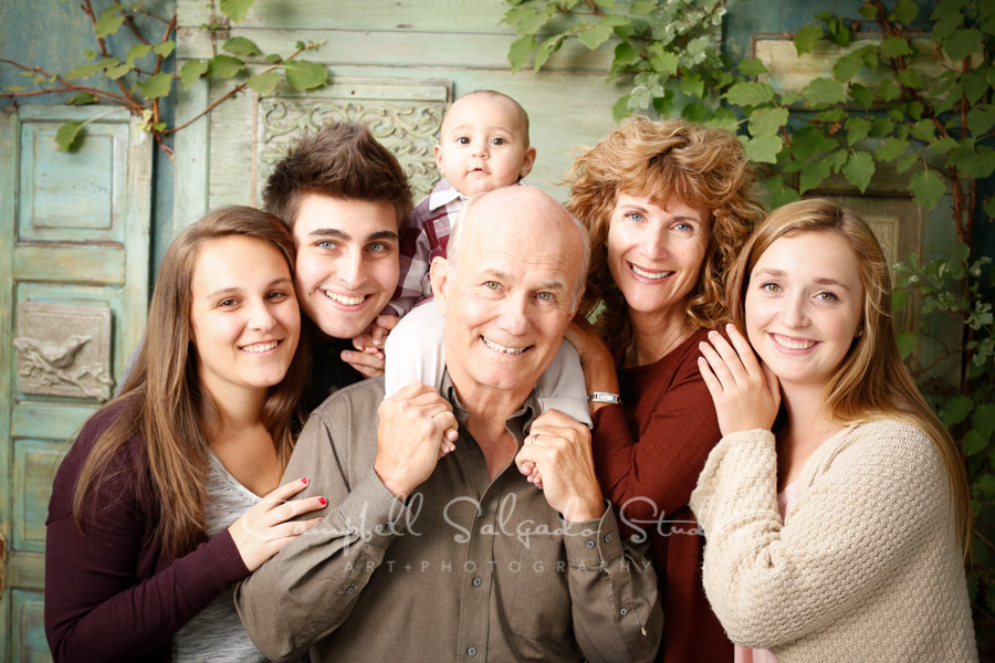 Portrait of multi-generational family on vintage green doors background by family photographers at Campbell Salgado Studio in Portland, Oregon.