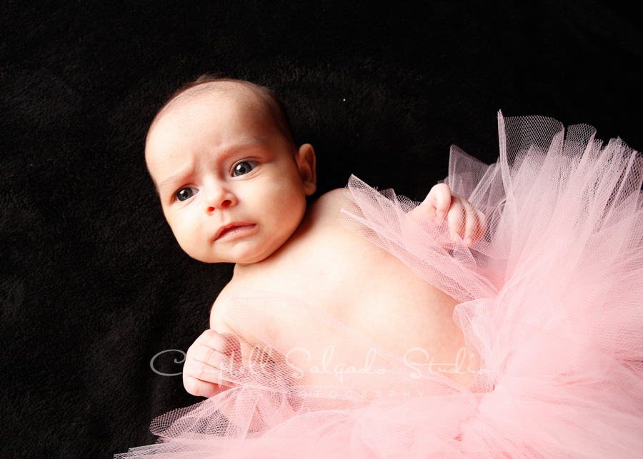 Portrait of baby on black background by children's photographers at Campbell Salgado Studio in Portland, Oregon.