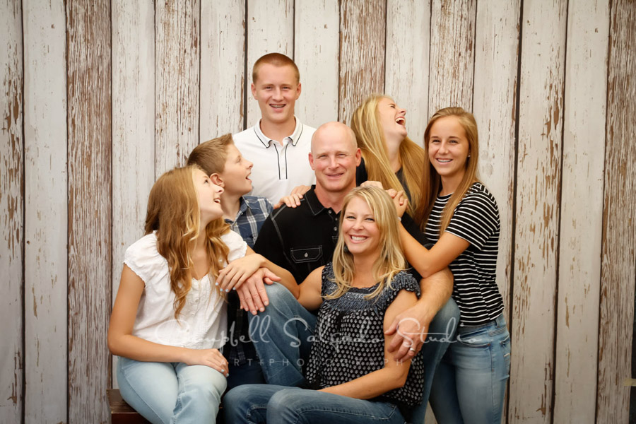 Portrait of family on white fence boards background by family photographers at Campbell Salgado Studio in Portland, Oregon.