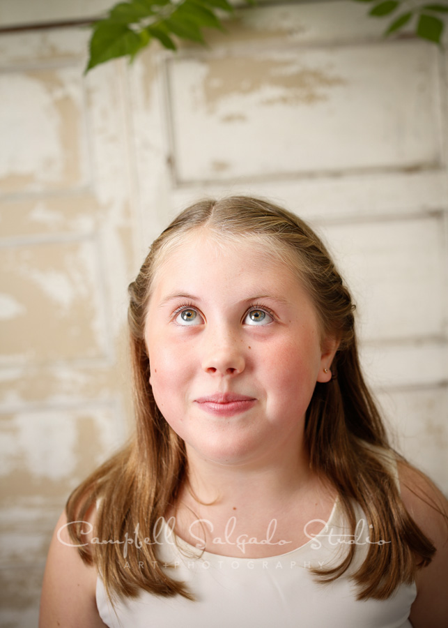 Portrait of girl on antique ivory doors background by childrens photographers at Campbell Salgado Studio in Portland, Oregon.