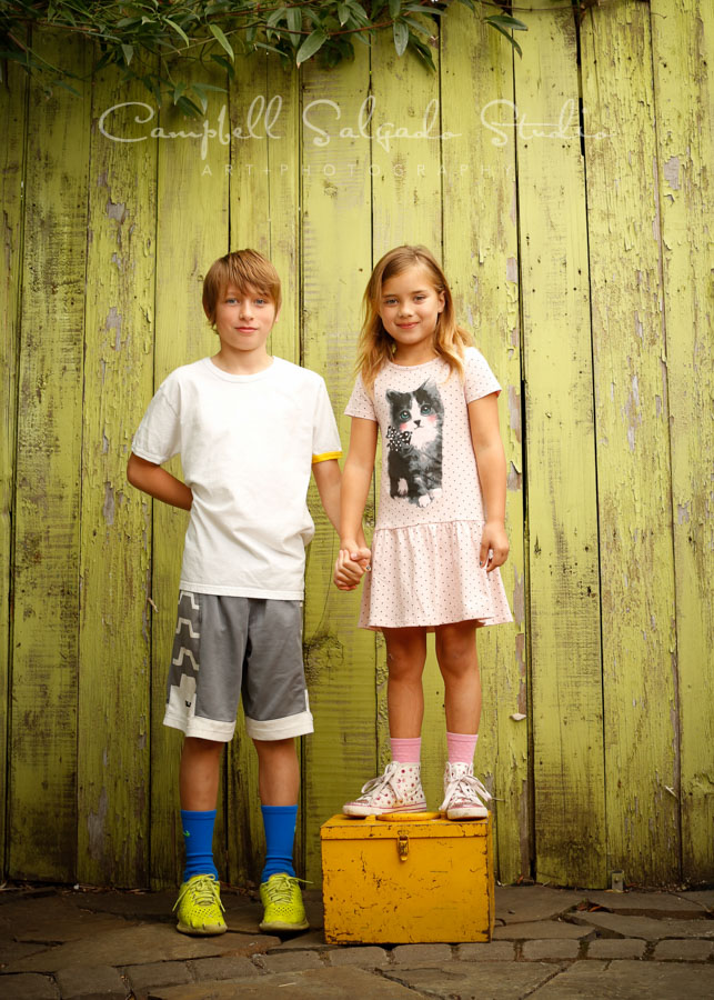 Portrait of kids on lime fenclboards background by child photographers at Campbell Salgado Studio in Portland, Oregon.