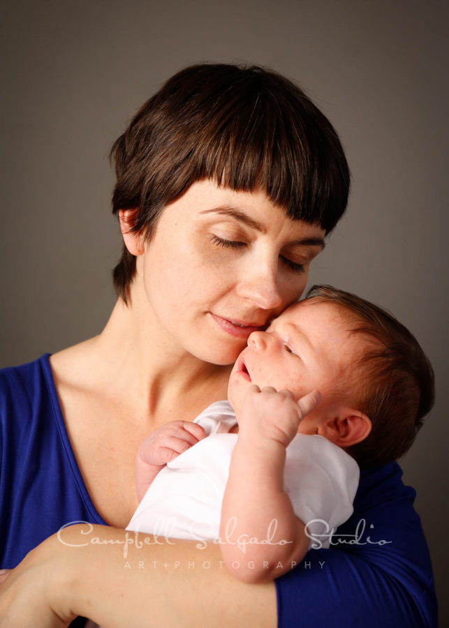 Portrait of mother and newborn on grey background by newborn photographers at Campbell Salgado Studio in Portland, Oregon.