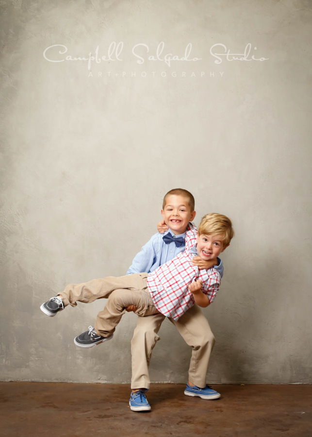 Portrait of brothers on modern gray background by child photographers at Campbell Salgado Studio in Portland, Oregon.