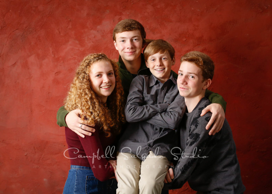 Portrait of kids on red stucco background by teen photographers at Campbell Salgado Studio in Portland, Oregon.
