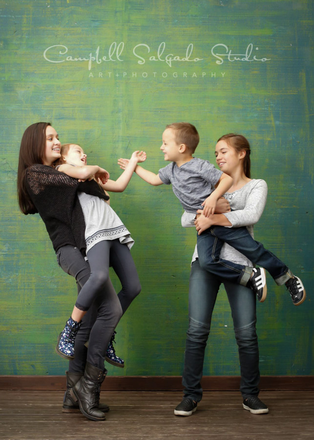 Portrait of children on blue-green weave background by child photographers at Campbell Salgado Studio in Portland, Oregon.