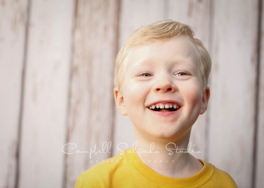 Portrait of boy on white fence boards background by child photographers at Campbell Salgado Studio in Portland, Oregon.