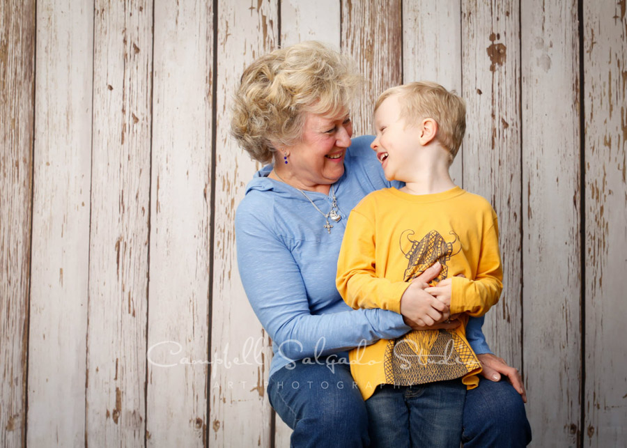 Portrait of grandmother and grandson on white fence boards background by family photographers at Campbell Salgado Studio in Portland, Oregon.