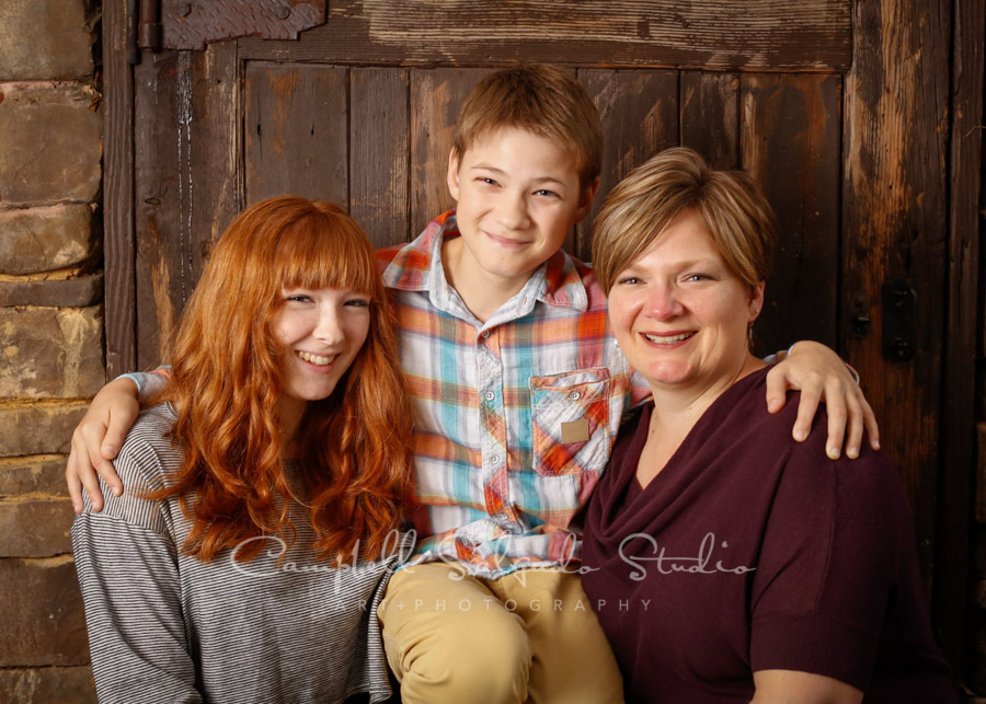 Portrait of family on rustic wooden door background by family photographers at Campbell Salgado Studio in Portland, Oregon.