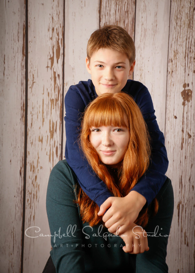 Portrait of siblings on white fence boards background by teen photographers at Campbell Salgado Studio in Portland, Oregon.