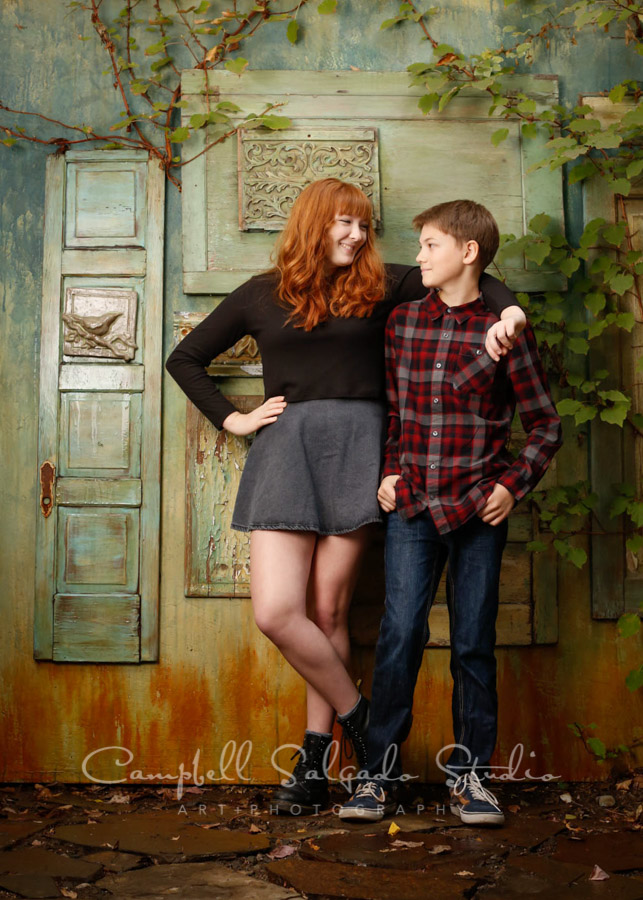 Portrait of siblings on vintage green doors background by teen photographers at Campbell Salgado Studio in Portland, Oregon.