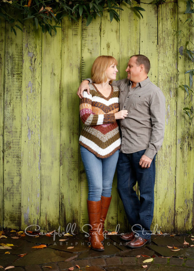 Portrait of couple on lime fence boards background by family photographers at Campbell Salgado Studio in Portland, Oregon.