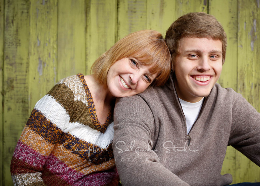 Portrait of mother and son on lime fence boards background by family photographers at Campbell Salgado Studio in Portland, Oregon.