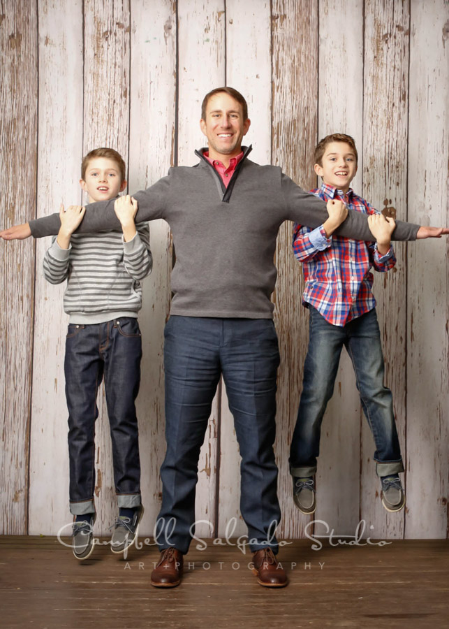 Portrait of dad and boys on white fence boards background by family photographers at Campbell Salgado Studio in Portland, Oregon.