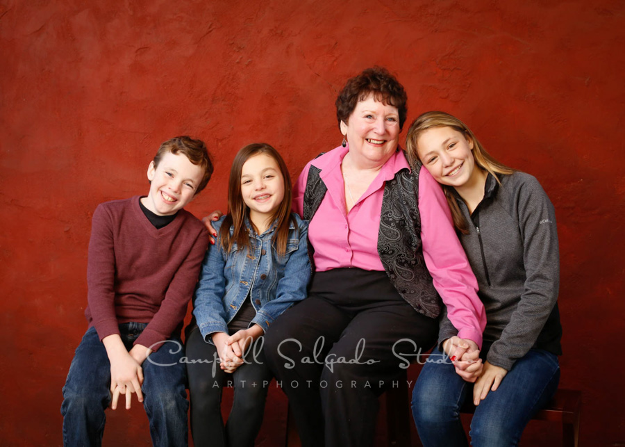 Portrait of grandmother and grandchildren on red stucco background by family photographers at Campbell Salgado Studio in Portland, Oregon.