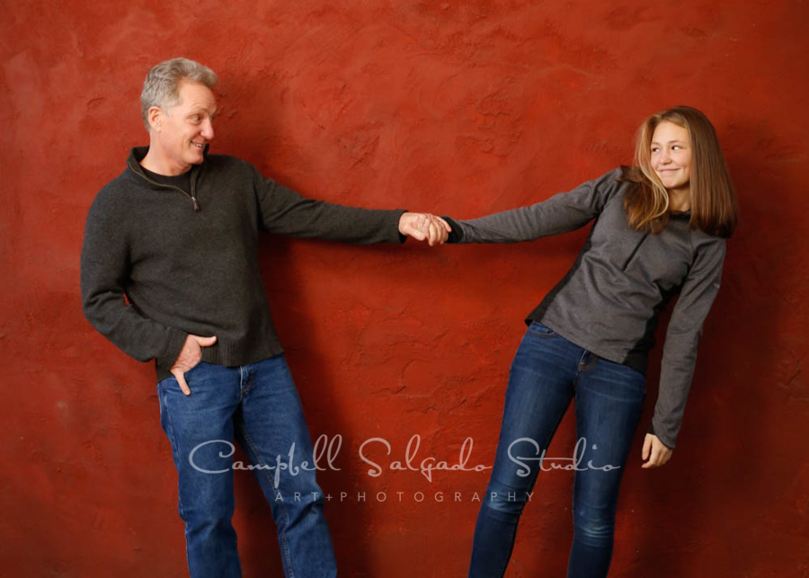 Portrait of father and daughter on red stucco background by family photographers at Campbell Salgado Studio in Portland, Oregon.