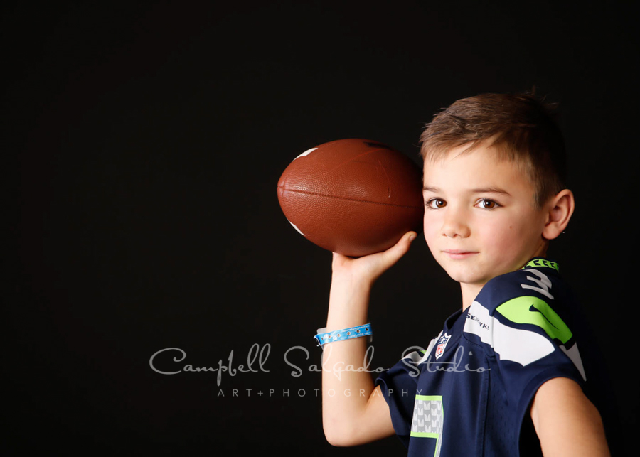 Portrait of boy with football on black background by child photographers at Campbell Salgado Studio in Portland, Oregon.