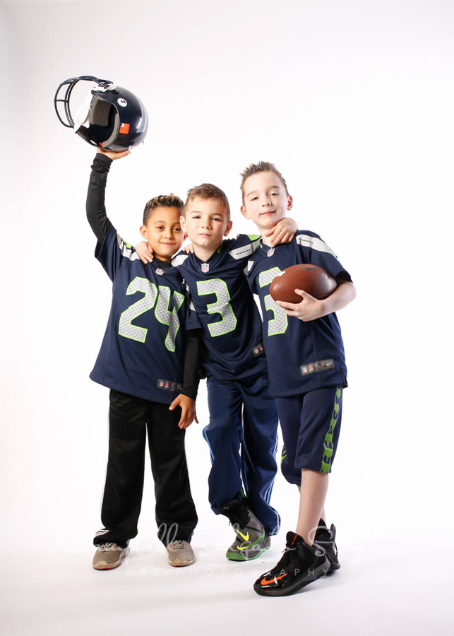 Portrait of boys in football gear on white background by children's photographers at Campbell Salgado Studio in Portland, Oregon.