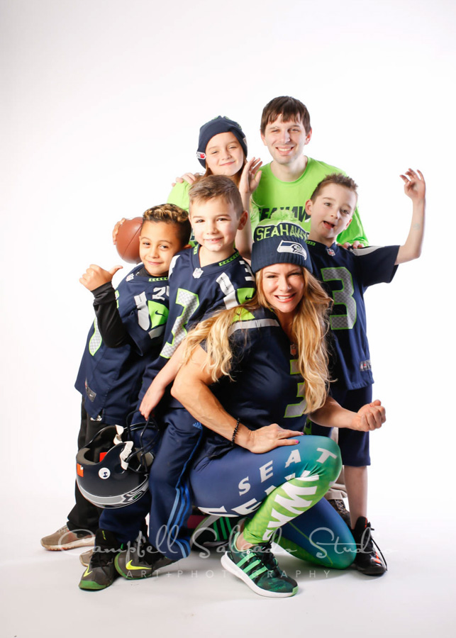 Portrait of family in football gear on white background by family photographers at Campbell Salgado Studio in Portland, Oregon.