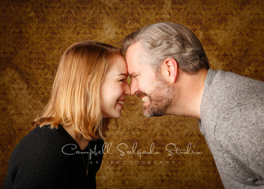 Portrait of father and daughter on amber light background by family portrait photographers at Campbell Salgado Studio in Portland, Oregon.